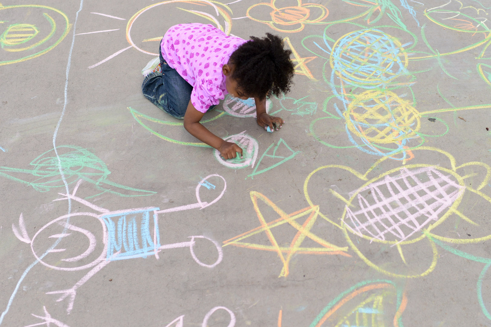 Play Matters - Girl draws on sidewalk with chalk