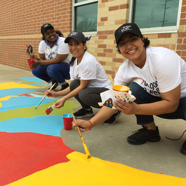 Volunteers paint a map of the US on asphalt at South Houston Elementary playground