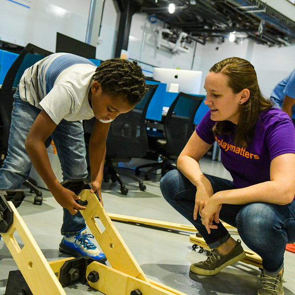 CarMax Foundation Future Innovators KABOOM! employee helps kid with Rigamajig