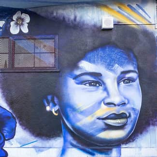 Painted mural of a young women with a lower to her right