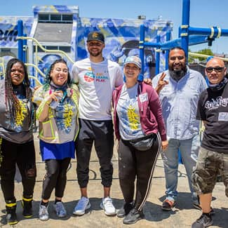 Stephen Curry poses with the mural artist and volunteers